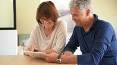 Senior couple at home using digital tablet - stock footage