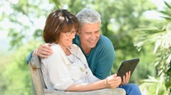 Senior couple using tablet in backyard - stock footage