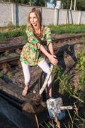 Pretty girl throws railway switch - stock photo