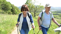Senior couple on a hiking day looking at map - stock footage