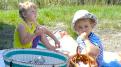 Children sitting on the grass outdoors and eat. Stock Footage