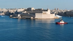 Pilot tag boat pulling cargo ship with with nice Valletta fortress view Stock Footage