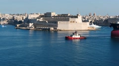 Large cargo ship transferring in Valletta port with beautiful fort view Stock Footage