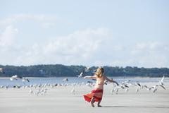 Girl running on beach amongst seagulls - stock photo