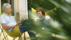 Senior couple relaxing in lawn chairs outside - stock footage