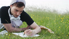 4K Casual man writing on a notepad in a meadow Stock Footage