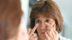 Senior woman applying eye concealer Stock Footage