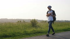 4K Male walking a country road playing his small guitar, in slow motion Stock Footage