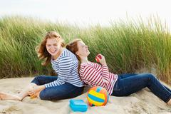 Teenagers laughing sitting in dunes Stock Photos
