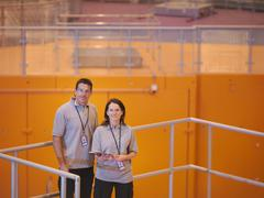Scientists standing on particle accelerator, looking to camera Stock Photos