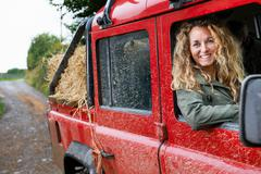Mother driving 4x4 on the farm - stock photo