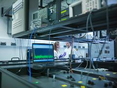 Scientists in laboratory with laser experiment - stock photo