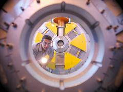 Male scientist inspects particle accelerator with a torch Stock Photos