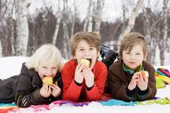 3 kids eating fruit Stock Photos
