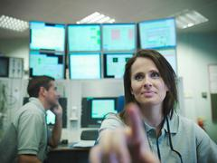 Scientists in particle accelerator control room. Female scientist in foreground, Stock Photos