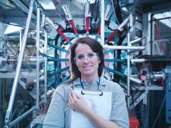 Female scientist with clipboard in front of particle accelerator Stock Photos