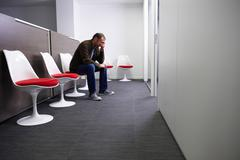 Man sitting in a doctor's waiting room - stock photo