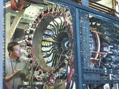 Male scientist inspects particle accelerator Stock Photos