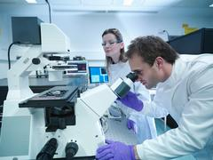 Scientists in lab coats using laser microscope Stock Photos