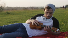 4K Young man playing a ukulele and tuning a string Arkistovideo