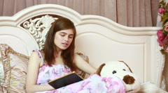 young girl in bed writing in a diary. poetry or prose - stock footage