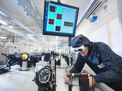 Male scientist in protective clothing and goggles setting up laser path in - stock photo