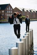 Man jumping from pole to pole Stock Photos