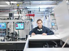 Male scientist in protective clothing looking to camera, next to laser equipment Kuvituskuvat