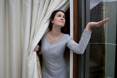 Woman checking for rain - stock photo