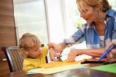 Woman doing handicraft with child Stock Photos