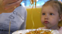 Mum and little baby child eating spaghetti pasta with chopsticks in fast food Stock Footage