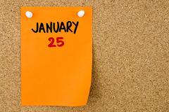 25 JANUARY written on orange paper note Stock Photos
