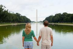 Rear view of young couple looking towards washington monument Stock Photos