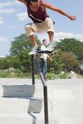 Skateboarder jumping over railing Stock Photos