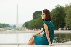 Girl by reflecting pool with washington monument in distance Stock Photos