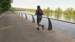 Old man training on embankment against river in the morning in slow motion Stock Footage