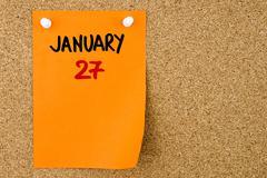 27 JANUARY written on orange paper note - stock photo