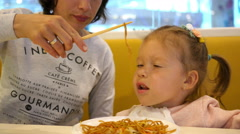 Mum feeds the little baby spaghetti pasta with chopsticks in a mall fast food - stock footage