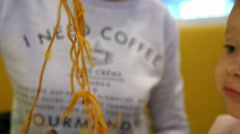 Mum and little baby child eating spaghetti pasta with chopsticks in fast food - stock footage