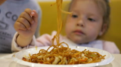 Mum feeds the little baby spaghetti pasta with chopsticks in a mall fast food Stock Footage