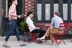 Waiter bringing coffee to men outside cafe Stock Photos