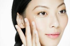 Young woman applying eye cream Stock Photos