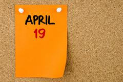 19 APRIL written on orange paper note - stock photo
