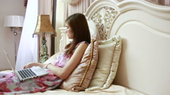 A young girl working on computer in bed. social networks Stock Footage