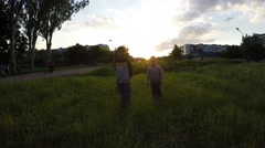 Two Happy Kids Running on Green Field over sunset - stock footage