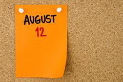 12 AUGUST written on orange paper note Stock Photos