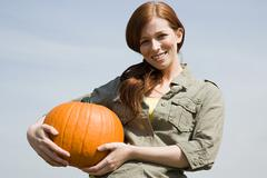 Young woman holding a pumpkin - stock photo