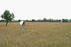 Young woman standing in poppy field with white parasol - stock photo