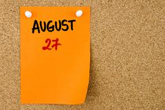 27 AUGUST written on orange paper note Stock Photos