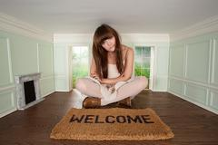 Young woman sitting in small room with welcome mat - stock photo